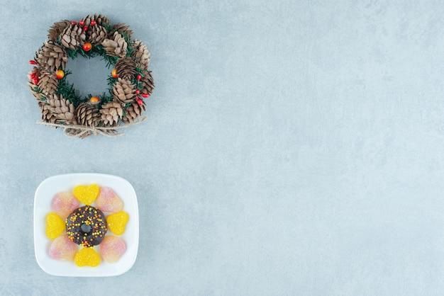 Grinalda de pinha e um prato de marmeladas e uma rosquinha em mármore.