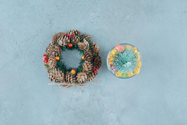 Grinalda de pinho e porta-bombons com nogulos e estatueta de árvore sobre mármore.