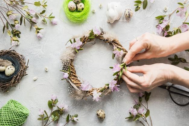 Grinalda de primavera com flores sobre a luz. lay criativo apartamento. vista do topo. decoração artesanal. mulher decorada.