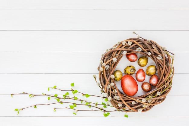 Grinalda de salgueiro de páscoa, ovos de páscoa, galhos de árvores de bétula em fundo branco de madeira