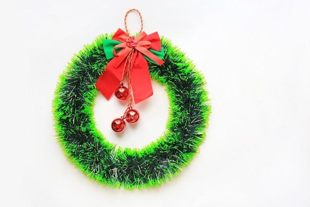 Grinalda redonda do natal com a fita e a bola vermelha que penduram no fundo branco.