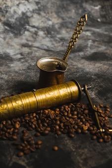 Grinder e cezve perto de grãos de café