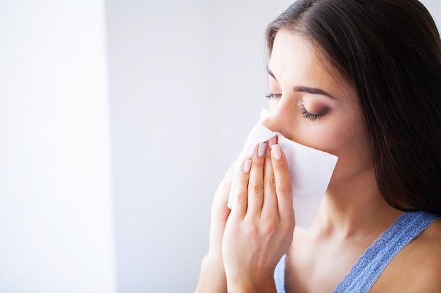 Gripe e mulher doente. mulher doente usando o tecido de papel, cabeça fria problema