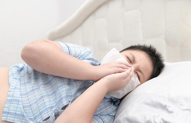 Gripe. menino obeso tem nariz alergia, gripe espirros nariz sentado na cama, conceito de cuidados de saúde