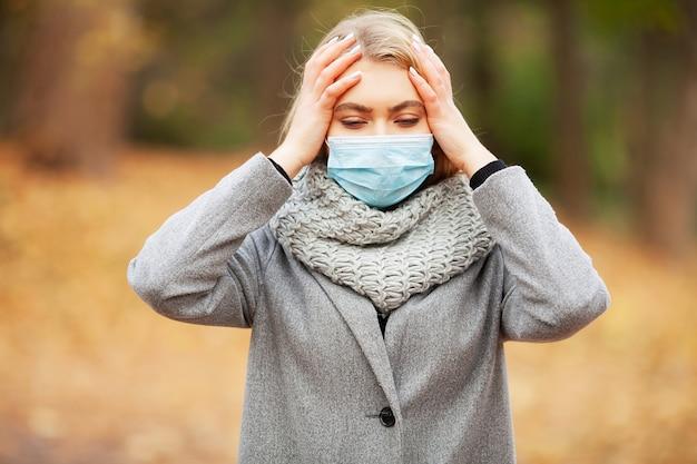 Gripes e resfriados. mulher com uma máscara médica no exterior