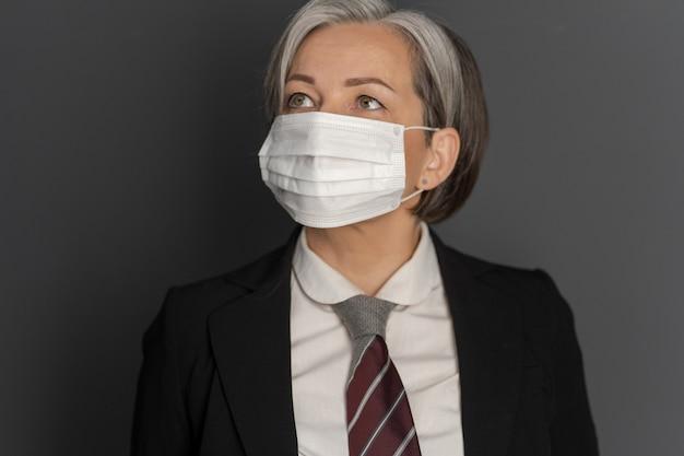 Grisalho meio envelhecido mulher de negócios na máscara protetora, olhando para cima. foco seletivo na máscara no rosto feminino. conceito de surto de vírus