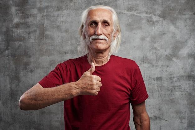 Grisalho moderno caucasiano velho com um bigode na camiseta vermelha aparece polegar e sorri, alegre rosto feliz contra a parede cinza