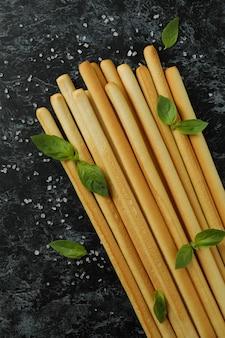 Grissini breadsticks com sal e manjericão em fundo preto esfumaçado