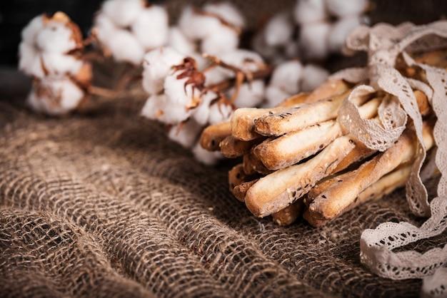 Grissini de palitos deliciosos. superfície de madeira escura e flores de serapilheira de algodão e renda de linho natural.