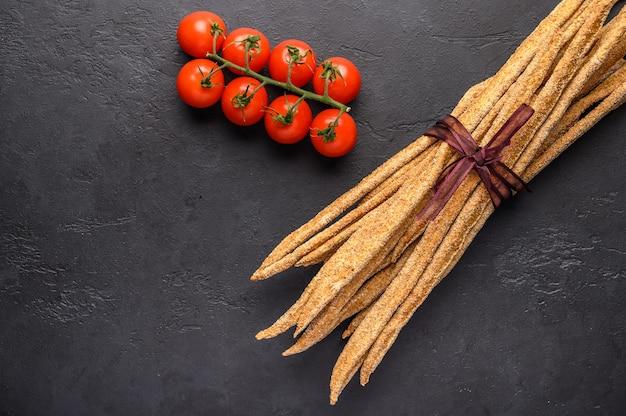 Grissini de pão de centeio tradicional italiano e tomate cereja em fundo escuro. Foto Premium