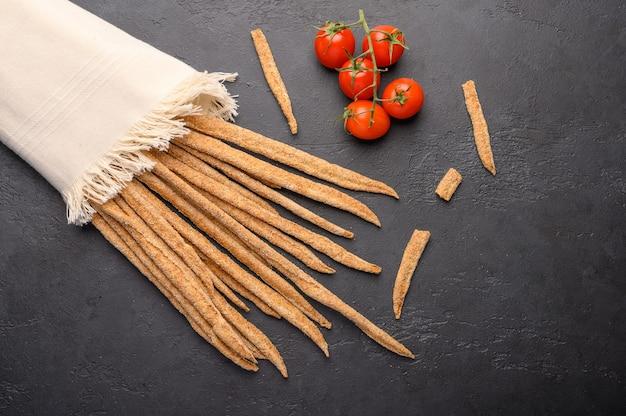 Grissini de pão de centeio tradicional italiano e tomate cereja em guardanapo de linho em fundo escuro.