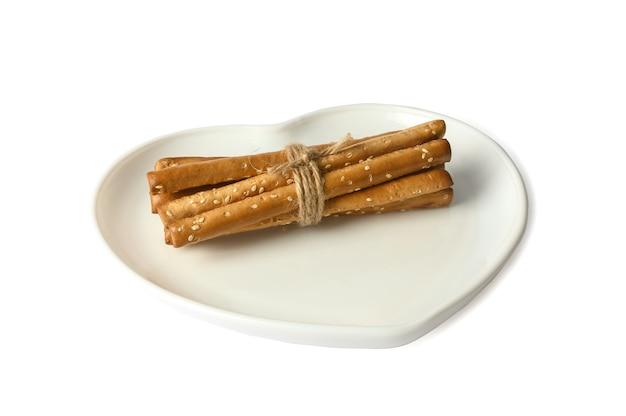 Grissini gruda em um prato branco em forma de coração. aperitivo delicioso crocante. sobre fundo branco.