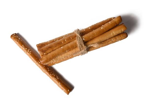Grissini mentira sobre um fundo branco. palitos brancos crocantes. biscoito com sementes de gergelim. o aperitivo é delicioso.
