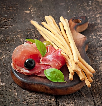 Grissini varas de pão com presunto, azeitonas, manjericão na madeira velha