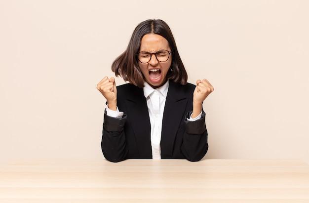 Gritando agressivamente com uma expressão de raiva ou com os punhos cerrados celebrando o sucesso