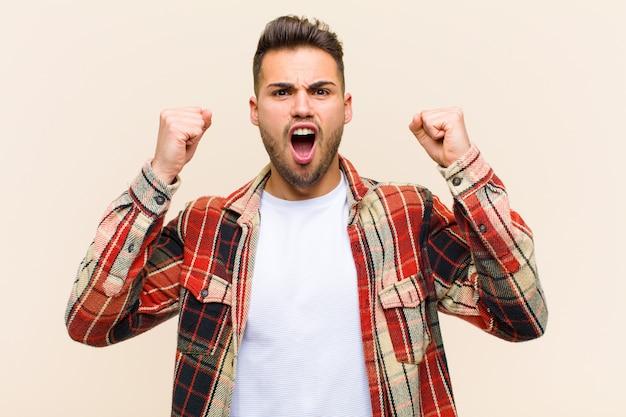Gritando agressivamente com uma expressão de raiva ou com os punhos cerrados comemorando o sucesso