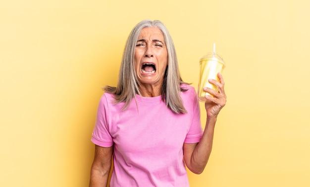 Gritando agressivamente, parecendo muito zangado, frustrado, indignado ou irritado, gritando não e segurando um milkshake
