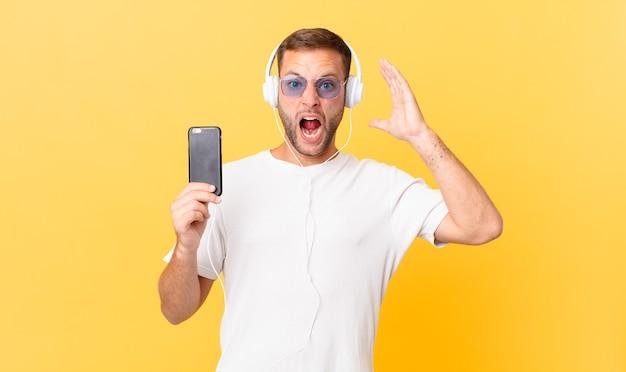 Gritando com as mãos ao alto, ouvindo música com fones de ouvido e um smartphone