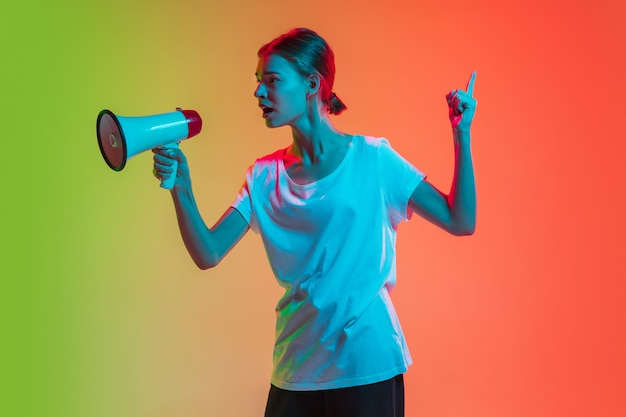 Gritando com megafone, alto-falante. retrato de jovem caucasiana em fundo gradiente estúdio verde-laranja em luz de néon. conceito de juventude, emoções humanas, expressão facial, vendas, anúncio.