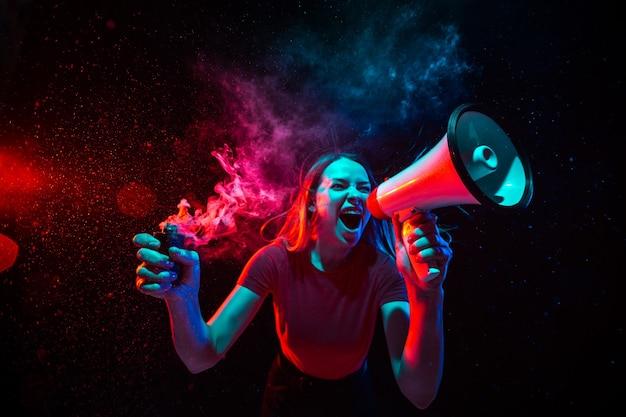 Gritando com megafone. jovem mulher com fumaça e luz de néon em fundo preto. altamente tenso, grande angular, visão de olho de peixe.