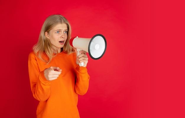Gritando com megafone. retrato de uma jovem mulher caucasiana em fundo vermelho studio com copyspace. linda modelo feminino. conceito de emoções humanas, expressão facial, vendas, anúncio, juventude. folheto