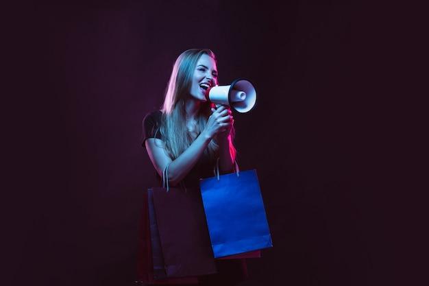 Gritando com sacolas de compras para vendas. retrato de jovem em luz de néon no fundo escuro. as emoções humanas, sexta-feira negra, cyber segunda-feira, compras, vendas, conceito de finanças.