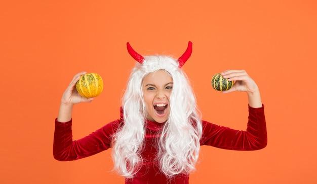 Gritando criança do diabo com cabelo branco segurar abóbora vegetal usar fantasia de chifres de diabinho na festa de halloween, feliz dia das bruxas.