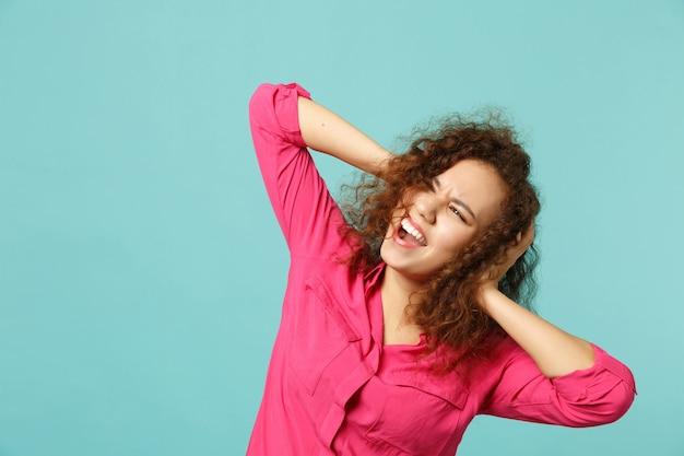 Gritando garota africana em roupas casuais rosa, olhando de lado, colocando as mãos na cabeça isolada no fundo da parede azul turquesa no estúdio. emoções sinceras de pessoas, conceito de estilo de vida. simule o espaço da cópia.