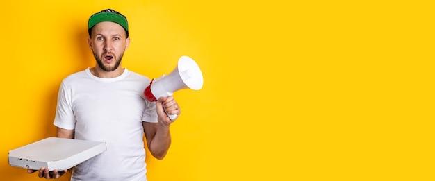Gritando jovem com megafone segurando pizza embalada na superfície amarela. bandeira.