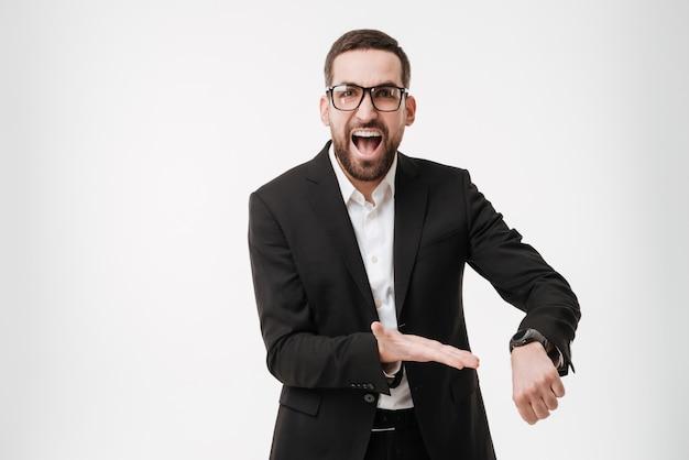 Gritando jovem empresário barbudo mostrando o relógio.