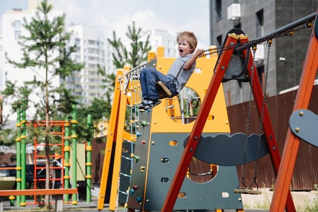 Gritando menino andando em balanços em um parquinho infantil. ele está voando alto, dobrando os apoios da corrente.