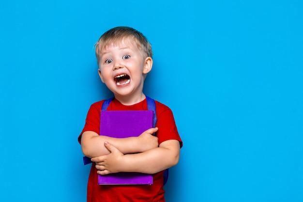 Gritando menino com livro e mochila, chateado surpreso e com medo da escola. de volta à escola