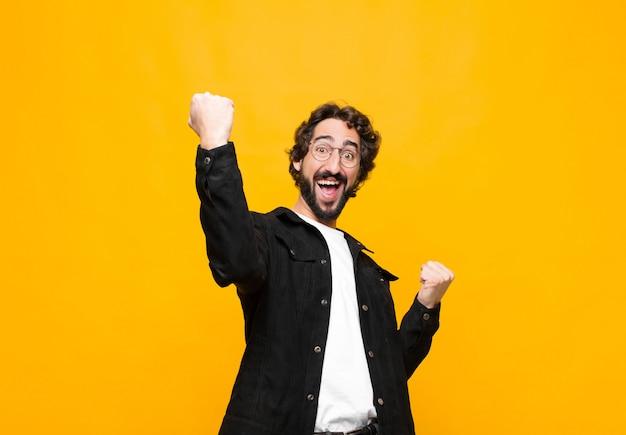 Gritando triunfantemente, parecendo um vencedor animado, feliz e surpreso, comemorando