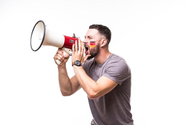 Grite no megafone, fã de futebol da alemanha, no jogo de apoio da seleção da alemanha em fundo branco. conceito de fãs de futebol.