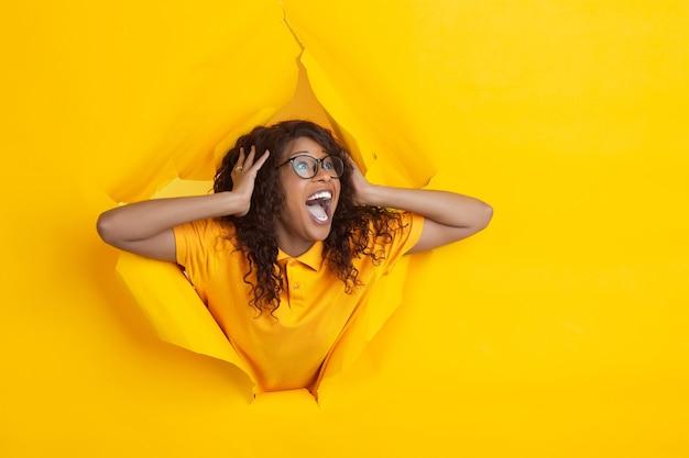 Grito de espanto. jovem afro-americana alegre em fundo de papel amarelo rasgado, emocional, expressivo. rompendo, descoberta. conceito de emoções humanas, expressão facial, vendas, anúncio.