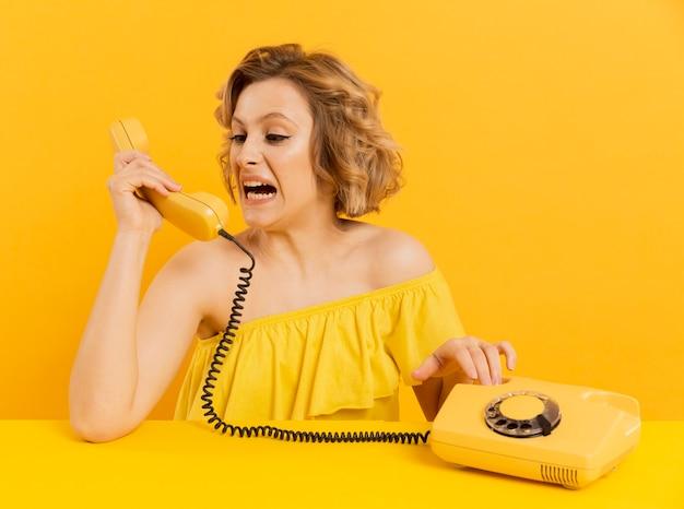Gritos nervosos da mulher na conversa de telefone velha