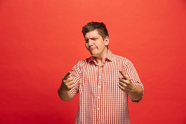 Gritos, ódio, raiva. chorando homem irritado emocional, gritando sobre fundo vermelho do estúdio. rosto jovem e emocional. retrato de meio corpo masculino.