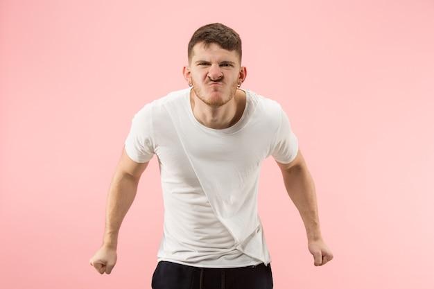 Gritos, ódio, raiva. chorando homem zangado emocional gritando no fundo rosa do estúdio. rosto jovem e emocional. retrato de meio corpo masculino. emoções humanas, conceito de expressão facial. cores da moda