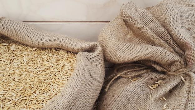 Grões de aveia no saco de serapilheira, close-up. grãos de malte ou trigo. conceito de alimentos e agricultura