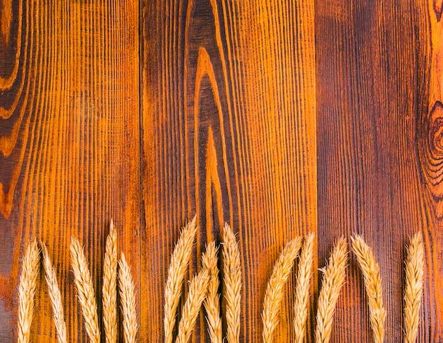 Grões de trigo no fundo da prancha de madeira.
