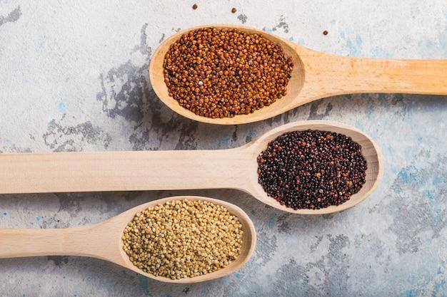 Grões pretas, vermelhas e brancas do quinoa em uma colher de madeira no branco. comida saudável sem glúten. closeup de quinoa chenopodium