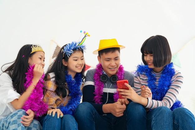 Grop menina e menino adolescentes jogando em telefones celulares, estilo hippie, estudantes, amigos, segurando o smartphone, depois de selfie