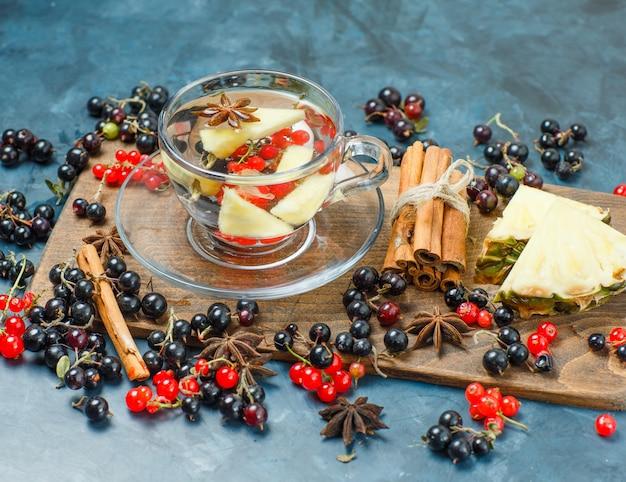 Groselha com especiarias, abacaxi, bebida, vista de alto ângulo em azul escuro e tábua de cortar