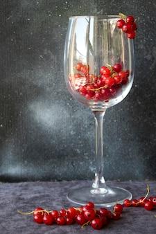 Groselha no copo de vinho no fundo cinza e azul. grande grupo de frutas coloridas.