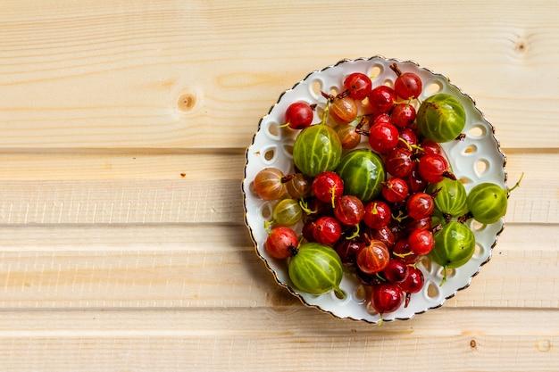 Groselhas no prato. amoras frescas. groselha verde vermelha no fundo de madeira.