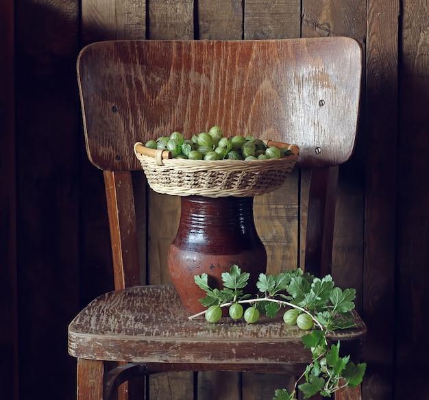 Groselhas verdes em uma cesta na cadeira. ainda vida com as groselhas nas placas do fundo.