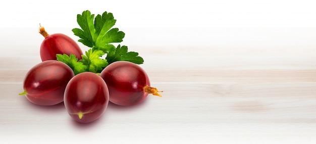 Groselhas vermelhas espinhosas vermelhas deliciosas (ribes hirtellum - rode gooseberry) em de madeira.