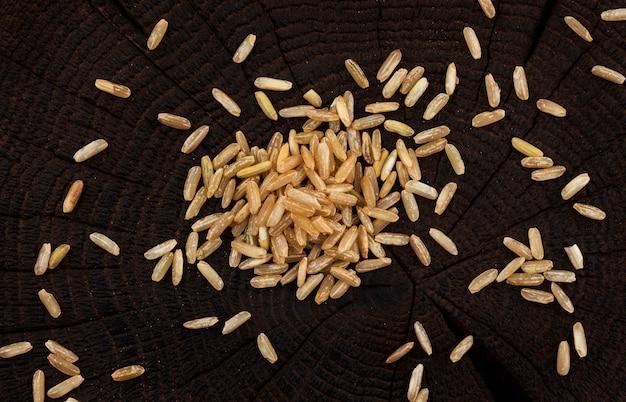 Grumos de arroz integral em preto de madeira, vista superior