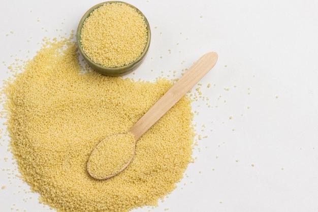 Grumos, fonte de cuscuz de fibra alimentar. colher de pau e caixa. carboidratos saudáveis. Foto Premium