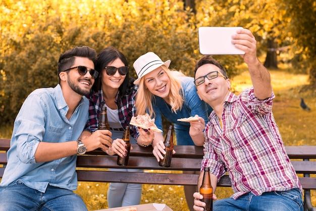 Grupo alegre de amigos tirando uma selfie enquanto bebe cerveja e come pizza